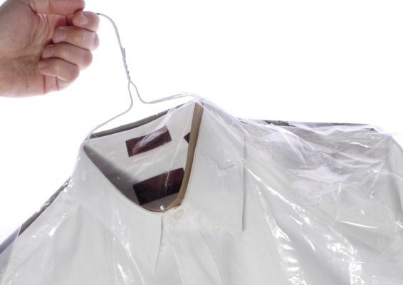 A hand holding laundered shirts on hangers.